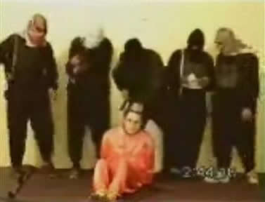 An image made from a video posted on May 11 on an Islamic militant Web site affiliated with al-Qaida showing a group of five men wearing headscarves and black ski masks standing over a bound man in an orange jumpsuit, identified as Nick Berg