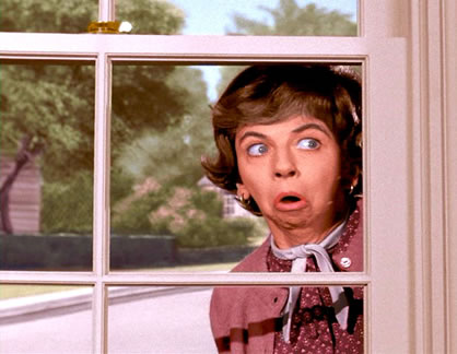Mrs. Kravitz peering out a window with an appalled look on her face